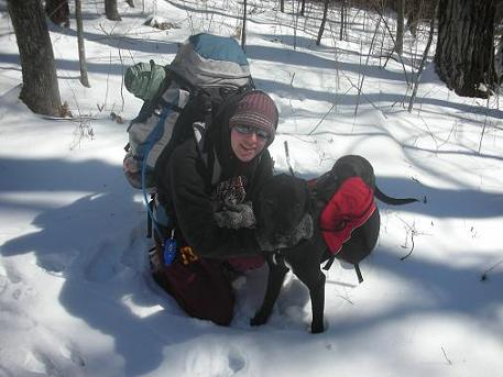 Woman in the snow wearing a backpack with her black lab wearing a dog backpack - going winter camping with her dog!
